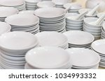 stack of clean white plates and ... | Shutterstock . vector #1034993332