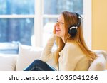 happy young woman listening to...   Shutterstock . vector #1035041266