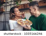 mixed race couple eating pizza... | Shutterstock . vector #1035166246