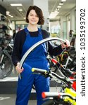 Small photo of Portrait of adult happy repairwoman standing near cycle in bicycle store