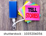 Small photo of Tell Stories. Business concept for Storytelling Telling Story written on sticky note with space on old wood wooden background with power bank