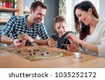 Happy family playing board game ...