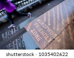 """Small photo of A jogger crosses a grated bridge with a river below. Sign reads """"Acrophobia Friendly Zone"""""""