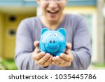 happy asian man holding blue... | Shutterstock . vector #1035445786