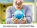 happy asian man holding blue... | Shutterstock . vector #1035445786