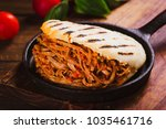 Small photo of Freshly cooked Arepa with roasted meat on wood table
