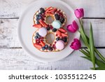 Small photo of Homemade cake in shape of number 8 decorated with white cream and berries and flowers tulips. Sweet dessert as a gift for women's day on the eighth of March