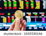 Small photo of Gold bitcoin on hand with blurred stock market data background
