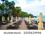 sun loungers on a beach in... | Shutterstock . vector #1035624946