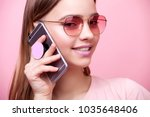 Small photo of Portrait of young beautiful woman isolated on pink background in t-shirt of the same color. An attractive smiling girl speaks on mobile phone on which is attached modern holder for phone pop socket