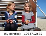 girls eat biscuits on the beach | Shutterstock . vector #1035712672