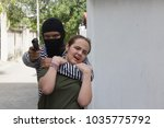 Small photo of The man wear stripes and wear veils carrying gun.The thief is locking the girl's neck as a hostage.Women wearing green t-shirts are scared.