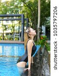 Small photo of portrait of young woman relaxing in swimming pool, enjoy weather in tropical country on background of apartment building on sunny day with sunshine. Concept of enjoying life, tratement for healthy