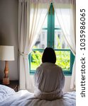 lone woman sitting on the bed... | Shutterstock . vector #1035986065