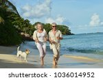 elderly couple running  on beach | Shutterstock . vector #1036014952