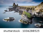 West coast sea cliffs of Snaefellsnes Peninsula on Iceland in long exposure photo. Pure blue water with high cliffs above sea. Beautiful colourful scenic view of basalt rock reef.