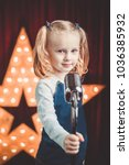 Small photo of A girl with a microphone learns to sing. the child is singing on stage