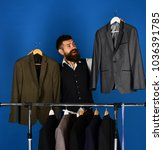 man with beard by clothes rack. ... | Shutterstock . vector #1036391785