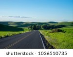 highway among wheat fields in... | Shutterstock . vector #1036510735