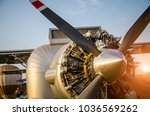 Small photo of Aeronautical festival.Detailed engine of silver aircraft and airscrew of modern turboprop airplane standing on parking place and air balloons background with sunlight.