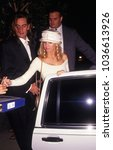Small photo of Los Angeles, California - exact date unknown; circa 1990: actress Heather Locklear signing an autograph before entering limousine with rocker Tommy Lee in the background