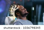 Stock photo in laboratory man wearing brainwave scanning headset sits in a chair with closed eyes monitors 1036798345