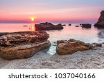 Huge stones in the water with bright blue and pink sunrise sky in the sea beach, Odessa, Ukraine