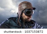 Old plane pilot on background of storm clouds with expressive face. glasses and old hat with black leather jacket - stock photo