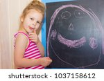 Small photo of The child draws his mother on the slate. A little girl is drawing on the blackboard.