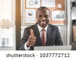 Small photo of Undeniable success. Portrait of cheerful young elegant businessman is sitting at table and smiling. He is feeling gladness while giving thumbs-up to camera