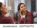 young woman applying makeup on... | Shutterstock . vector #1037926792