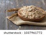 oat flakes or oatmeal in wooden ...   Shutterstock . vector #1037961772