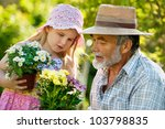 Happy grandfather with his granddaughter working in the garden - stock photo