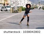 young fit black woman on roller ... | Shutterstock . vector #1038042802