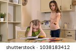 Small photo of Strict mother criticizing daughter for mistakes in homework, lack of support