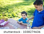 brothers coloring easter eggs | Shutterstock . vector #1038274636