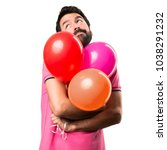 Small photo of Handsome young man making unimportant gesture and holding balloons over isolated white background