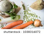 Small photo of flat lay vegetables, celeriac, carrots, union, leeks, ingredients for Dutch traditional food snert, split peas soup. White table, pan, green leaves background