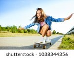 smiling woman riding longboard... | Shutterstock . vector #1038344356