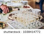 waiter pouring champagne in... | Shutterstock . vector #1038414772