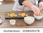 chef hands putting ginger from...   Shutterstock . vector #1038420178