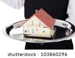 Close-up  of a butler with model of a house on tray. Isolated on white - stock photo