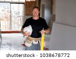 attractive and confident constructor carpenter or builder man with protective helmet posing happy working at industrial construction site in installation and renovation blue collar work industry - stock photo
