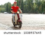 Small photo of Man driving down a paved road on a motorcycle. Uplifted mood of a worker loving his job. Pizza delivery.