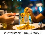 spaghetti on a fork. hand of... | Shutterstock . vector #1038975076