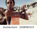 African woman stretching arms at the beach. Fitness female doing warmup workout and looking away outdoors. Closeup shot.