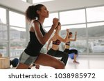 young woman in sportswear doing ... | Shutterstock . vector #1038985972