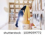 a woman with a child puts the... | Shutterstock . vector #1039059772