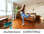 woman dances while cleaning an... | Shutterstock . vector #1039070962