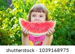 a child eats watermelon.... | Shutterstock . vector #1039168975